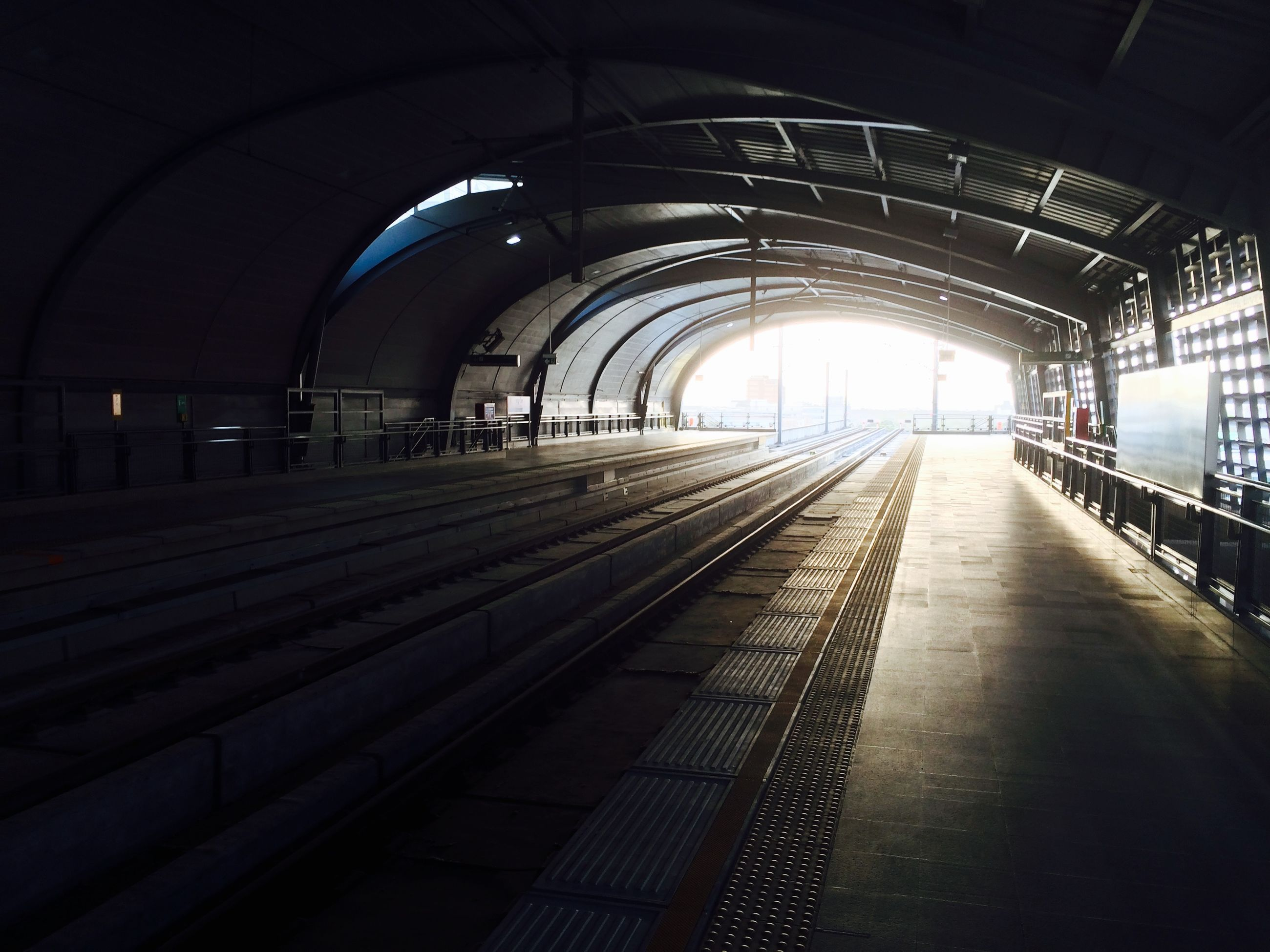 indoors, transportation, railroad station, the way forward, railroad track, rail transportation, public transportation, railroad station platform, diminishing perspective, ceiling, architecture, built structure, illuminated, vanishing point, empty, incidental people, arch, subway, subway station, interior