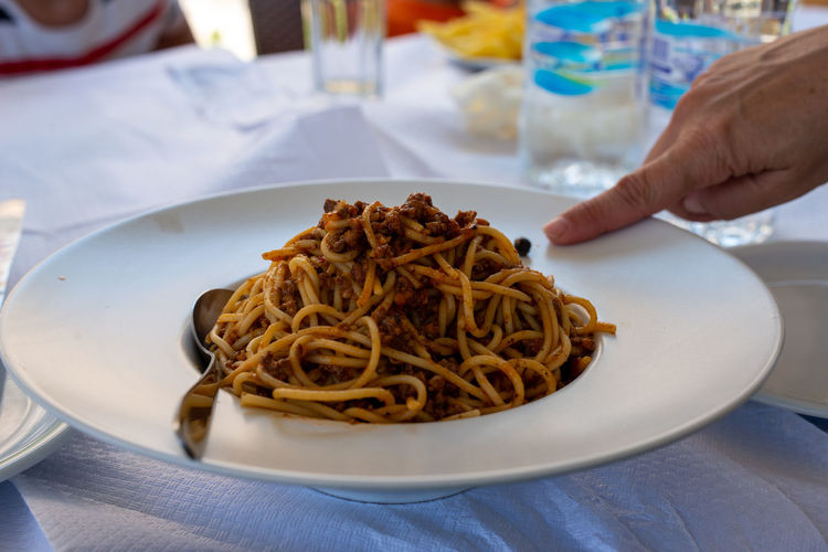 Plate full of spaghetti bolognese. finger pointing at food.