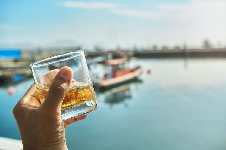Male hand holding glass whiskey the beginning of summer at marina, summer concept.