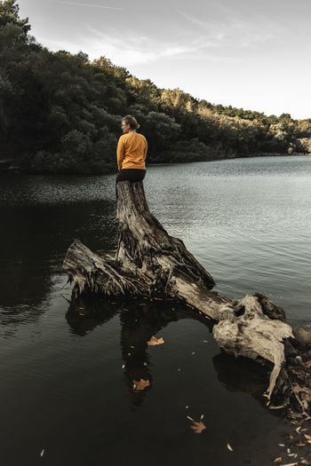 Reflection of man in lake against sky