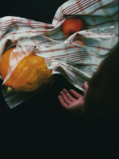 Close-up of hand, kitchen towel and pumpkin