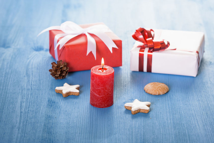 Christmas decor with small gift boxes, gingerbread cookies, and a lit red candle Candle Celebration Christmas Decoration Gifting Time Gingerbread Cookie Handmade Gifts Lit Candle No People Self-made Gift Sharing  Still Life
