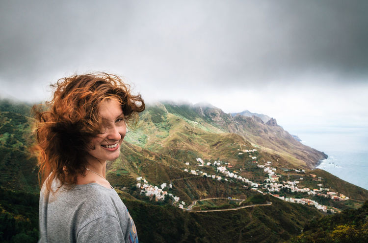 Joyful young woman with flying hair hidden her face looks at the camera in front of Taganana village on north of Tenerife. Concept of travelling, happiness, freedom. Traveler are enjoying the landscape, Canary Islands, Spain Canarias Canary Islands Casual Clothing Cloud - Sky Emotion Hair Hairstyle Happiness Leisure Activity Mountain Mountain Range One Person Outdoors Portrait Sky Smiling Spain ✈️🇪🇸 Tenerife Young Adult