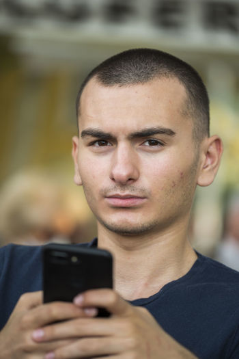Portrait of serious teenage boy using mobile phone