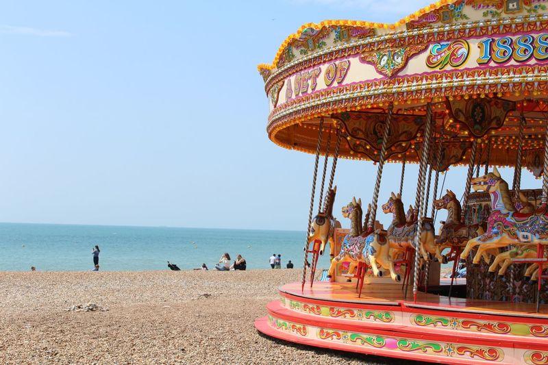 Carousel at sea against clear sky