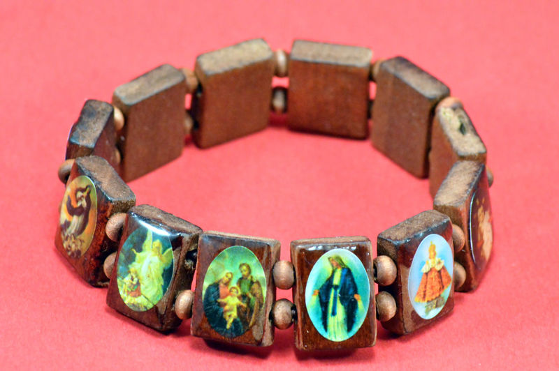 Close-up of religious bracelet on red background