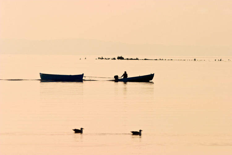 Fisherman in a pleasure boat at sunset
