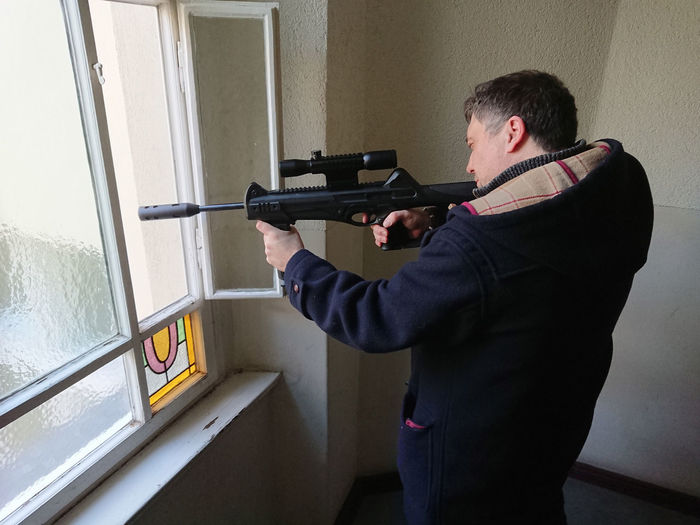 Man Aiming Sniper Rifle Through Window