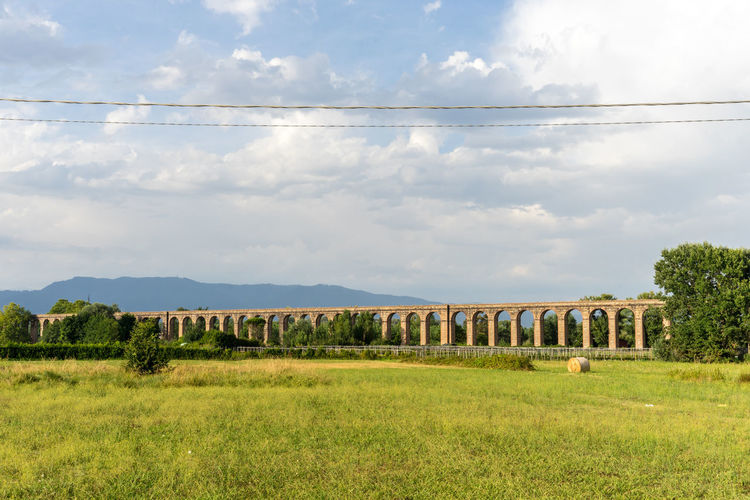 Aqueduct in tuscany, Italy Aqueduct Architecture Bridge Built Structure Cloud - Sky Connection Day Environment Field Grass Green Color Land Landscape Nature No People Outdoors Plant Rail Transportation Scenics - Nature Sky Tree