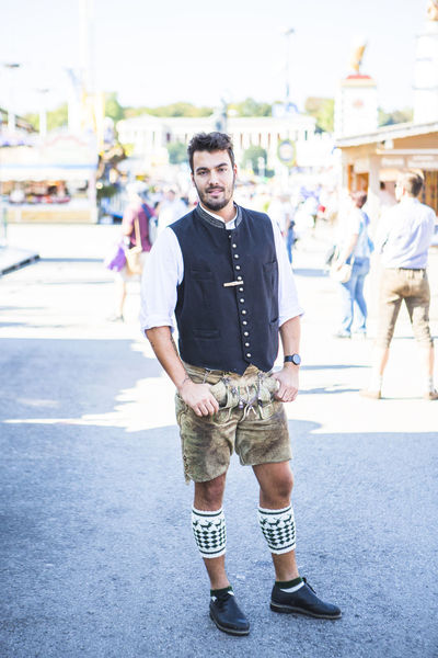 A young man wearing Lederhosen poses in front of the camera at the Octoberfest in Munich, Germany 30-40 Years Adult Beard Brown Hair Excitement Festival German Clothing Germany Going Out Happy Jacket Leather Lederhosen Leg Warmers Munich München Octoberfest Party Portrait Portrait Of A Man  Real People Style Theresienwiese Trend Young Man