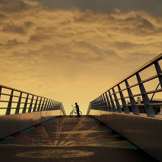 Mid distance view of man with bicycle on footbridge against sky during sunset