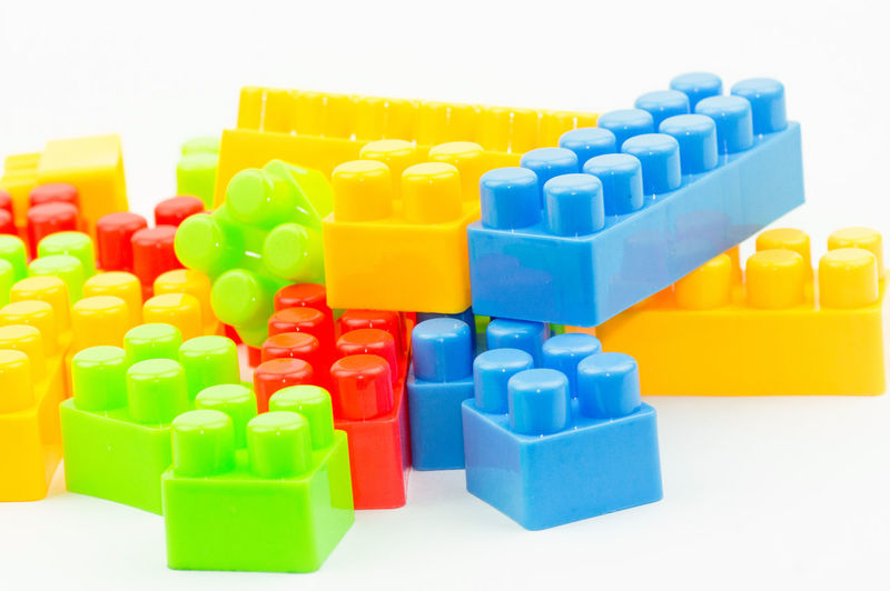 Close-Up Of Multi Colored Toy Blocks On White Background