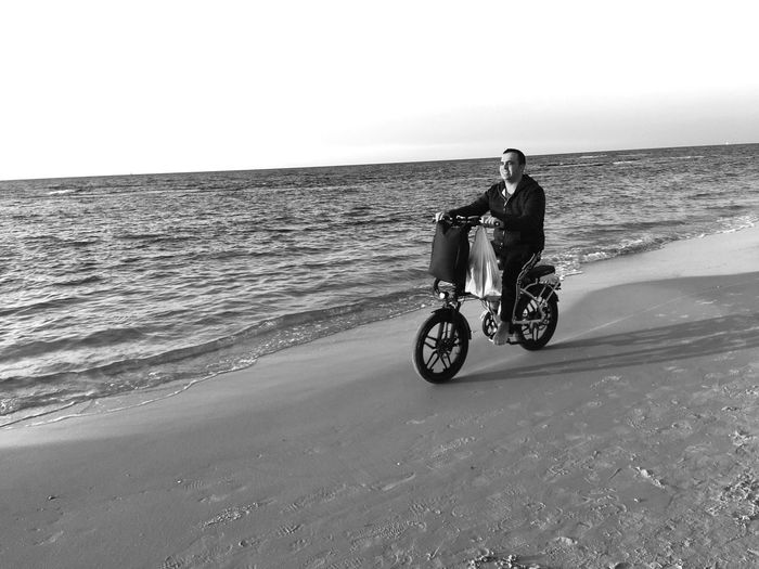 Man riding motorcycle on beach against clear sky