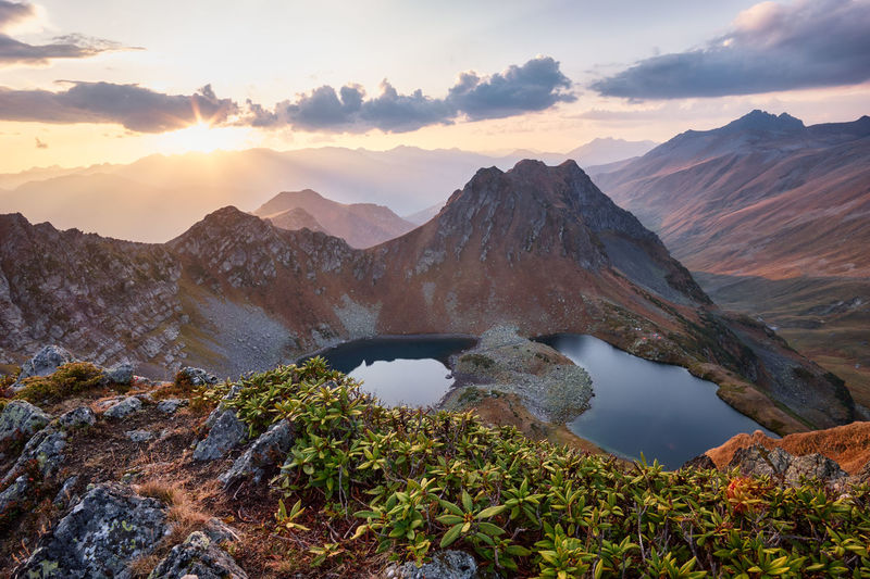 Beautiful mountains at sunset in clouds, gold alpine field, lakes and mountain ranges.