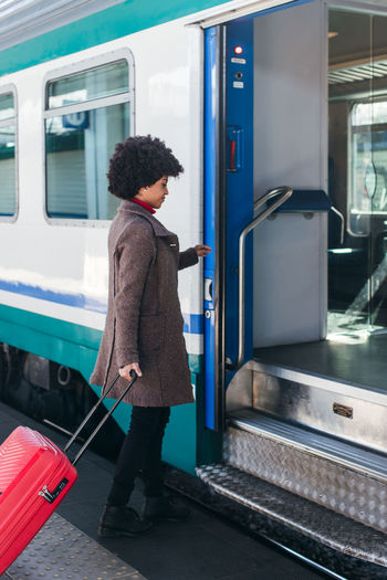 Woman standing on train at railroad station