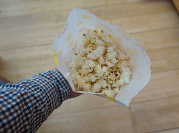 Cropped Image Of Hand Holding Popcorn At Home
