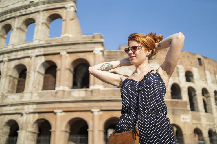 Happy woman standing against historic building