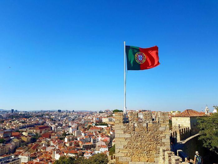 Portuguese flag waving on sao jorge castle against cityscape