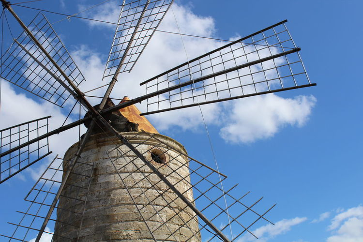 Low angle view of traditional windmill against cloudy blue sky on sunny day