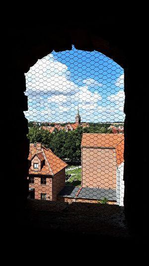 Buildings against sky seen through window