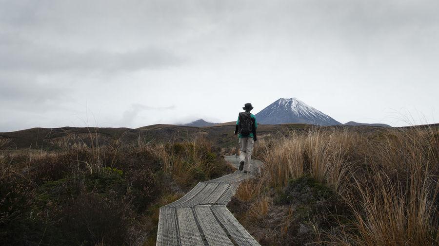 Rear view of man walking on footpath on field against sky