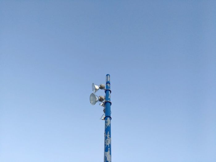 Low angle view of electric pole against clear blue sky