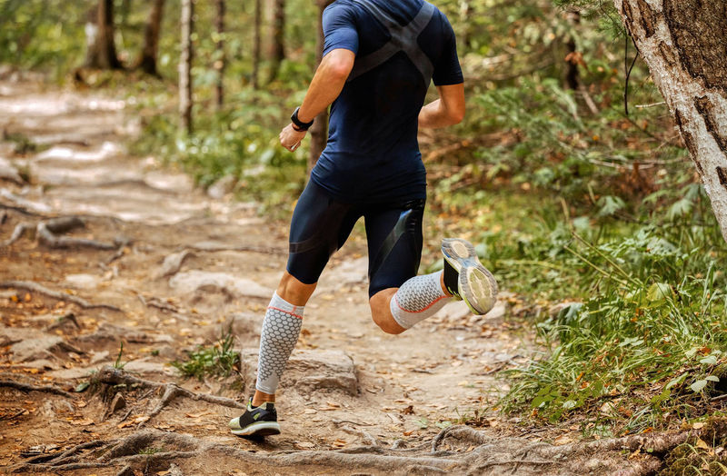 Low section of man running in forest