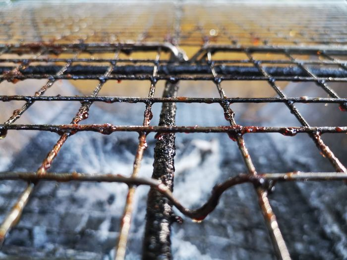 Close-up of snow on metal fence during winter