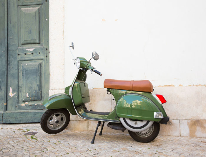 Side view of motor scooter against building