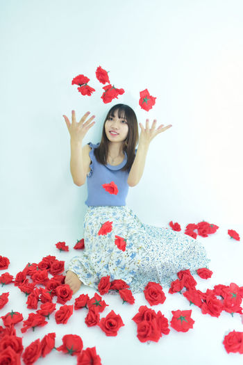 Portrait of woman with red flowers against white background