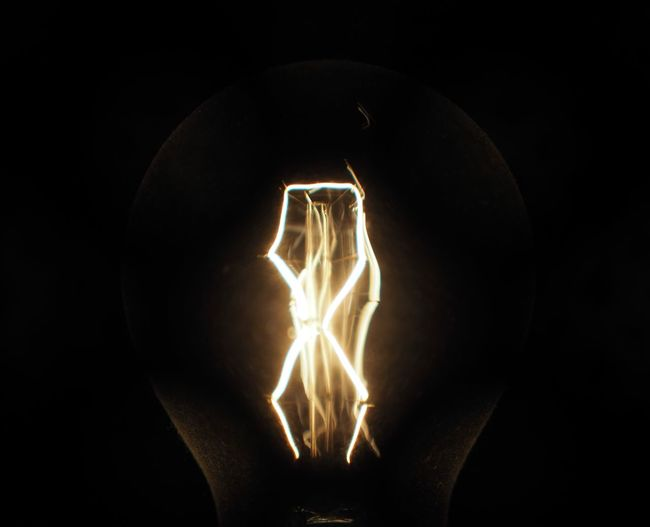 Close-up of lit light bulb in the dark