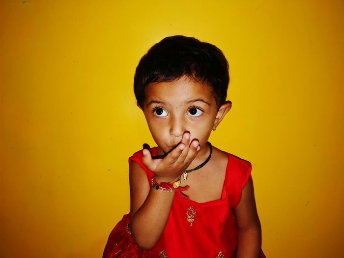 Girl Covering Mouth With Hand Against Yellow Background