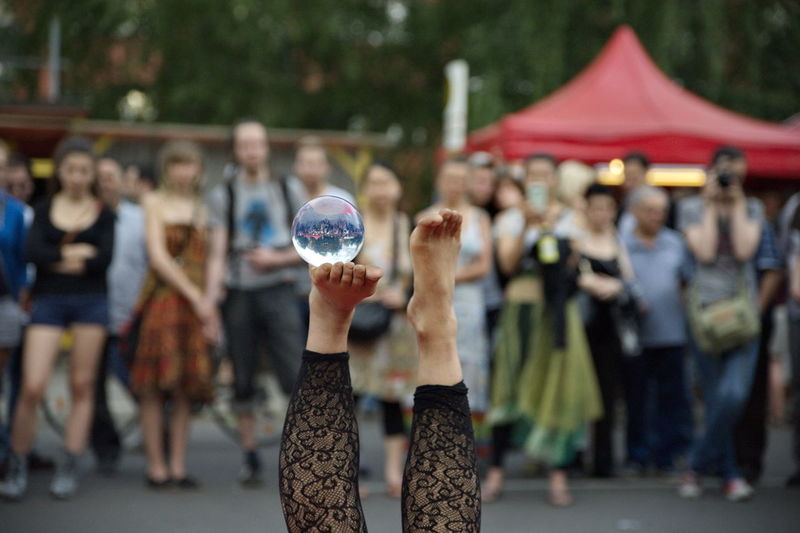 Low Section Of Street Performer Woman Balancing Crystal Ball On Foot
