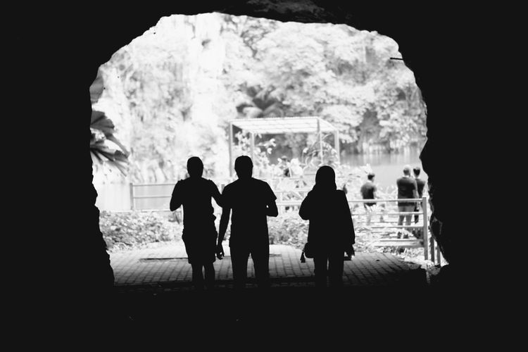 Silhouette people standing in cave