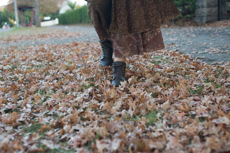 Low section of woman walking on autumn leaves