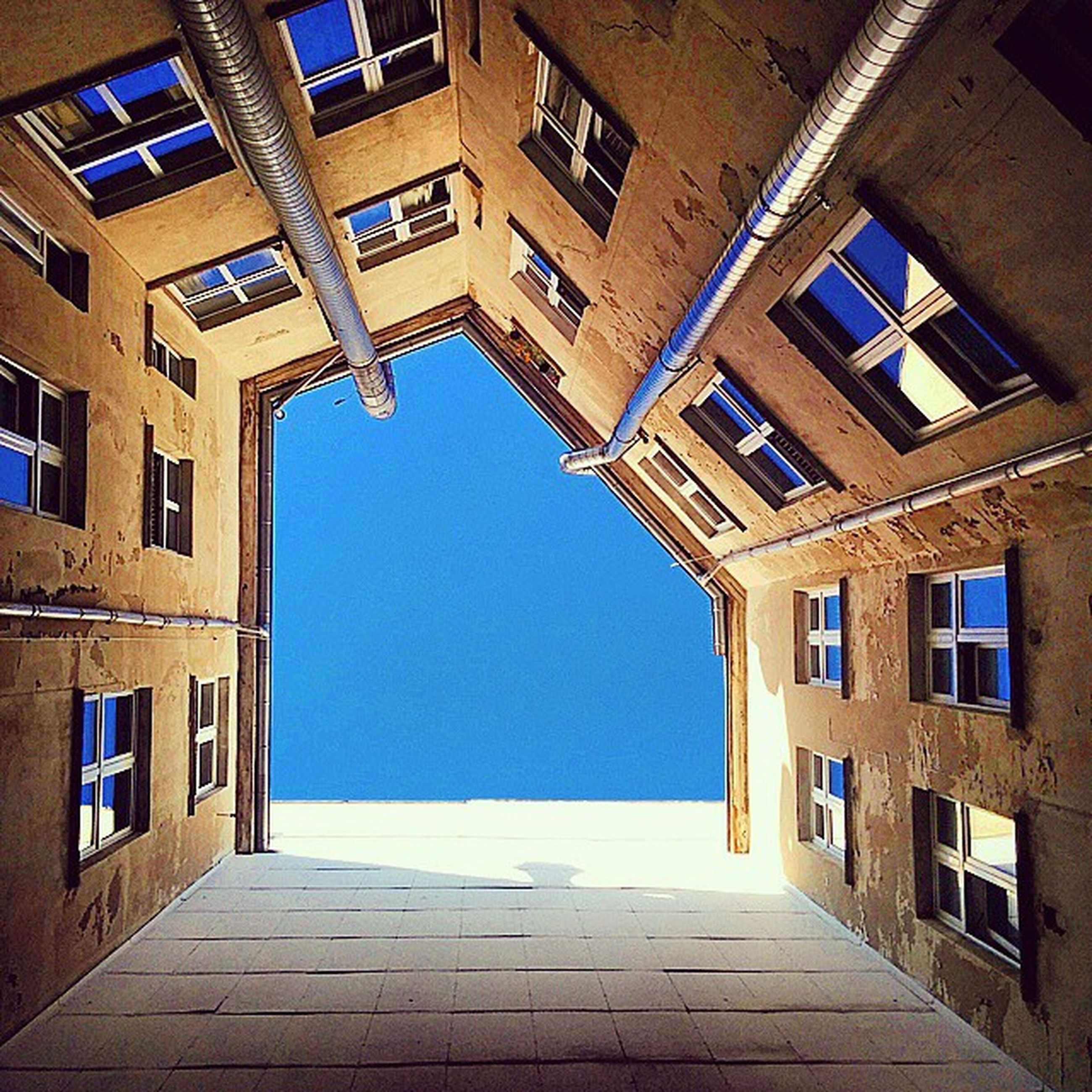 architecture, built structure, building exterior, window, blue, building, clear sky, residential structure, residential building, sunlight, house, day, city, no people, shadow, outdoors, low angle view, wall, door, facade