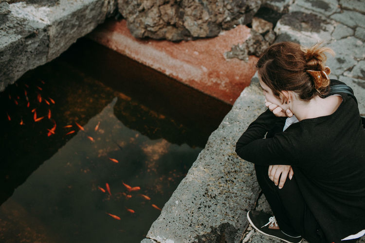 High Angle View Of Woman Looking At Fish In Pond