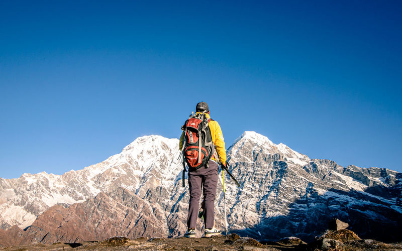 Man standing on mountain against blue sky