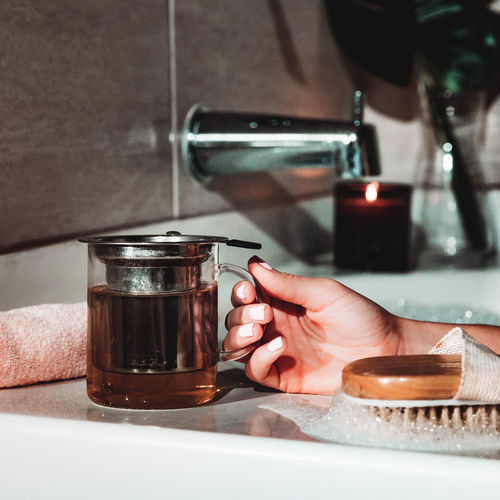 Cropped hand of woman having drink in bathtub