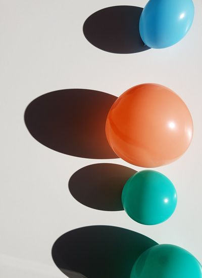 Multi colored balloons on white wall