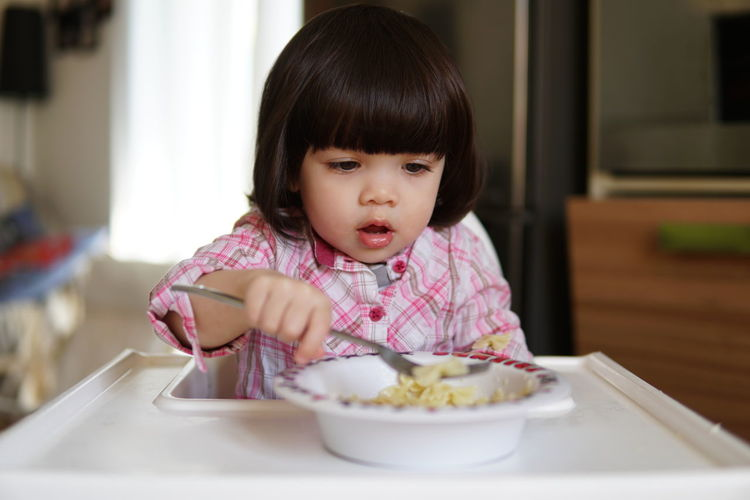 Close-up of cute baby girl eating food while sitting on high chair at home