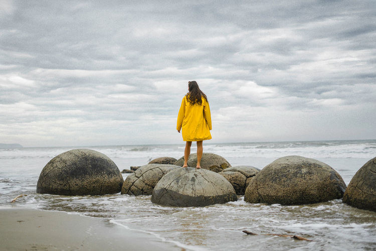 Yellow Yellow Jacket New Zealand Stones Beach Woman Water Cloud - Sky Sky Sea Beauty In Nature Solid Rock Nature Rear View Land Rock - Object One Person Scenics - Nature Standing Real People Day Full Length Outdoors Horizon Over Water