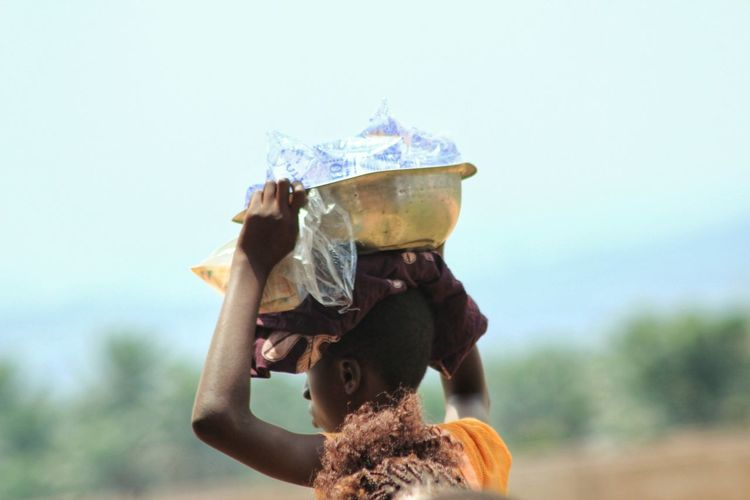 Close-Up Of Woman Carrying Container Against Sky