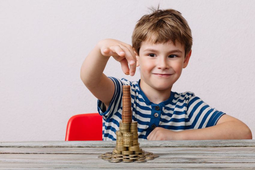 Boy stacking money to tower Boys Building Child Childhood Children Only Coin Currency Finance Front View Headshot Indoors  Intelligence Investing Males  One Boy Only One Person Playing Portrait Savings Stacking Wealth