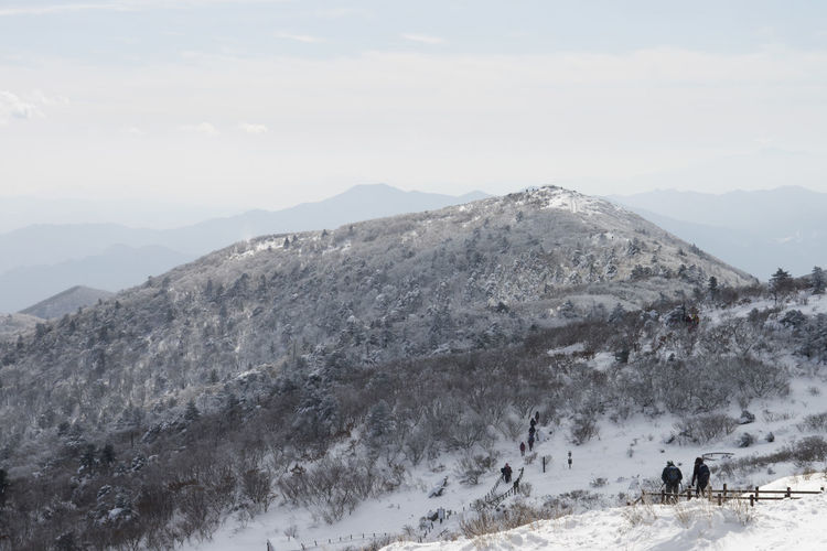 High angle view of people hiking on mountain against sky