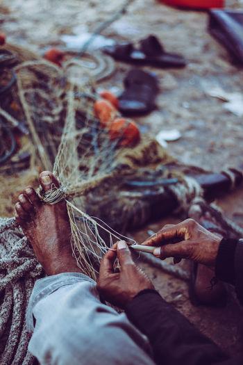 Close-up of man making fishing net
