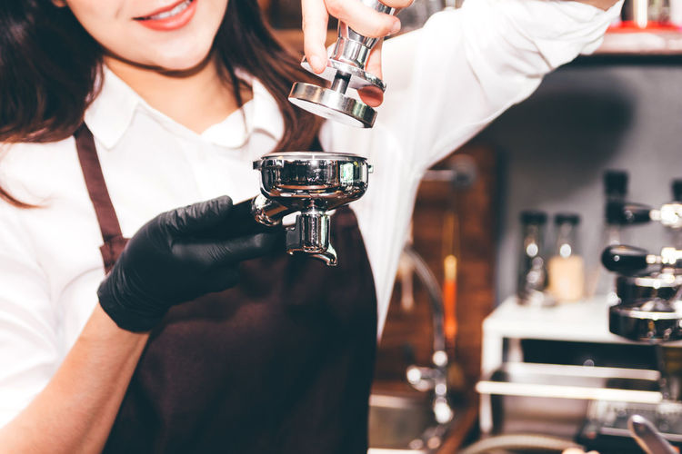 Barista using tamper to makes coffees in coffee bar Drink Refreshment Alcohol Food And Drink Bar - Drink Establishment Real People Indoors  Midsection Holding Focus On Foreground Front View Glass Occupation Lifestyles Women Bar Counter Standing Smiling Pouring Leisure Activity Bartender Happy Hour