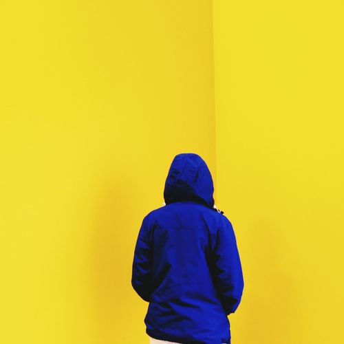 Rear View Of Person Standing Against Yellow Wall