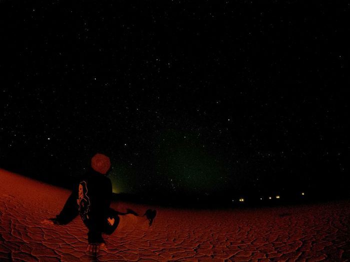 Rear View Of Person Sitting Against Star Field