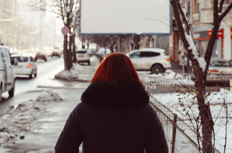 Rear view of woman on snow covered city during winter